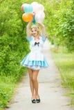 Mädchen, das mit einem großen Bündel bunten Ballonen aufwirft Stockfoto