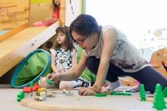 Mädchen, das mit einem hölzernen Zugstromkreis im Kindergarten spielt Stockbild