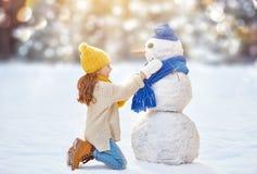Mädchen, das mit einem Schneemann spielt Stockfotos