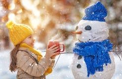 Mädchen, das mit einem Schneemann spielt Lizenzfreie Stockbilder