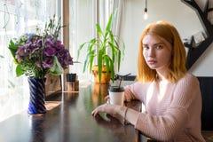 Mädchen, das mit einem Tasse Kaffee sitzt lizenzfreie stockfotografie