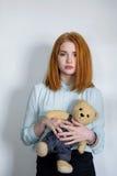 Mädchen, das mit einem Teddybären steht Lizenzfreies Stockbild