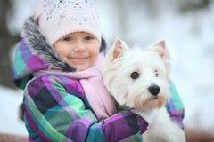 Mädchen, das mit einem weißen Hundewinterschnee spielt Lizenzfreie Stockbilder