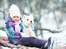 Mädchen, das mit einem weißen Hundewinterschnee spielt Lizenzfreie Stockfotografie