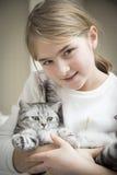 Mädchen, das mit einer britischen Katze spielt Stockfoto