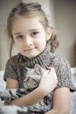 Mädchen, das mit einer britischen Katze spielt Lizenzfreies Stockbild