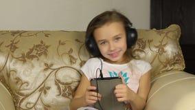 Mädchen, das mit einer Tablette sitzt und Musik auf Kopfhörern hört stock video footage