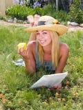 Mädchen, das mit einer Zeitschrift u. einem Apfel sich entspannt Stockfotografie