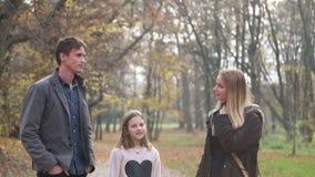 Mädchen, das mit Eltern während sie gehend in den Park spricht stock footage