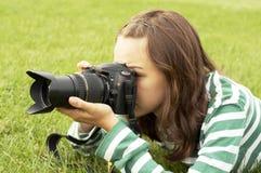 Mädchen, das mit Fotokamera liegt stockfotos