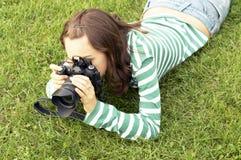 Mädchen, das mit Fotokamera liegt lizenzfreie stockbilder