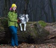 Mädchen, das mit heiserem Hund sitzt stockfotografie