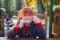Mädchen, das mit Herbstlaub spielt lizenzfreies stockbild