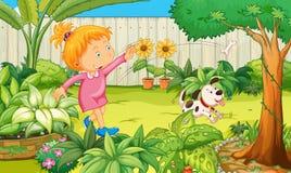 Mädchen, das mit Hund im Garten spielt Stockbild
