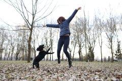 Mädchen, das mit Hund im Park spielt Sie beide, die in die Luft springen stockbild