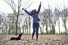 Mädchen, das mit Hund im Park spielt Das Mädchen springend in die Luft lizenzfreie stockfotos