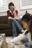 Mädchen, das mit Hund mit Mutter beim Anruf spielt stockfoto