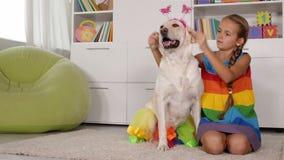 Mädchen, das mit Hund - oben ankleidend spielt stock footage