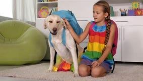 Mädchen, das mit Hund - mit Schultaschen auf ihren Rückseiten spielt stock video footage