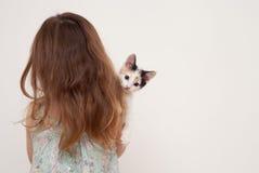 Mädchen, das mit ihr zurück steht und ein Kätzchen hält Lizenzfreie Stockbilder