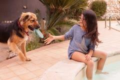 Mädchen, das mit ihrem Hund spielt stockbild