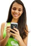 Mädchen, das mit ihrem Mobiltelefon lächelt Lizenzfreie Stockfotografie