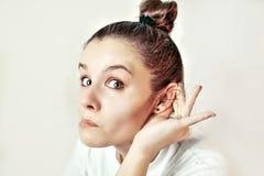 Mädchen, das mit ihrer Hand auf einem Ohr hört Stockfoto