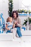 Mädchen, das mit ihrer Schwester nahe einem Weihnachtsbaum und einem Lächeln sitzt Stockbild