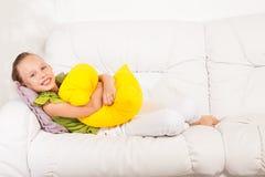 Mädchen, das mit Kissen legt Stockbilder