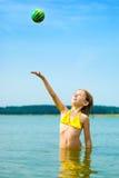 Mädchen, das mit Kugel im Wasser spielt Stockfotografie