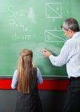 Mädchen, das mit Lehrer Wiping Board steht lizenzfreies stockbild