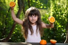Mädchen, das mit Orangen an einem Tisch in der Natur spielt Lizenzfreie Stockfotos