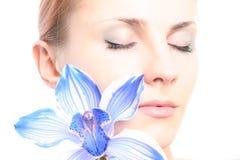 Mädchen, das mit Orchidee sich entspannt stockfoto