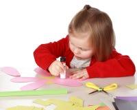 Mädchen, das mit Papier und Kleber spielt Lizenzfreies Stockfoto