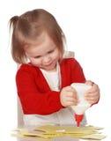Mädchen, das mit Papier und Kleber spielt stockbilder