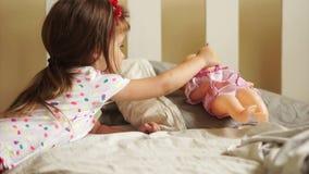 Mädchen, das mit Puppe spielt Sie setzte sie, um zu schlafen und gibt ihr einen Friedensstifter Glückliche Kindheit Kind-` s Spie stock video footage