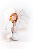 Mädchen, das mit Regenschirm und dem Lächeln sitzt Stockbild