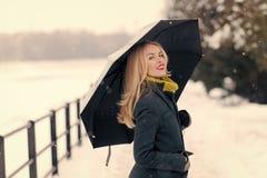 Mädchen, das mit Regenschirm am Wintertag geht Stockfoto