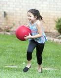 Mädchen, das mit rotem Ball läuft Lizenzfreies Stockfoto