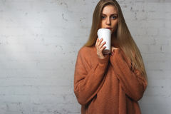 Mädchen, das mit Schalenkaffee in ihren Händen aufwirft Lizenzfreies Stockfoto