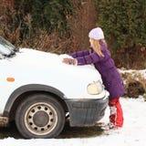 Mädchen, das mit Schnee auf Auto spielt Stockfotografie