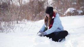 Mädchen, das mit Schnee spielt