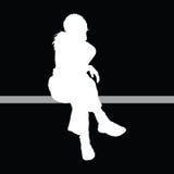 Mädchen, das mit schwarzem Hintergrund sitzt Lizenzfreie Stockfotos