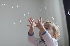 Mädchen, das mit Seifen-Luftblasen spielt Lizenzfreie Stockfotografie