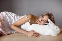 Mädchen, das mit seinem großes Kaninchen des Haustieres schläft Lizenzfreies Stockbild