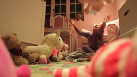 Mädchen, das mit Spielwaren in Schlafzimmer-tragenden Pyjamas spielt stock video