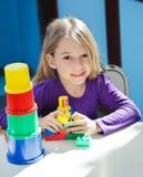 Mädchen, das mit Spielwaren am Schreibtisch in der Vorschule sitzt Lizenzfreie Stockbilder