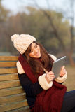 Mädchen, das mit Tablette auf Bank im Park sitzt Stockbilder