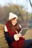 Mädchen, das mit Tablette auf Bank im Park sitzt Stockfotografie