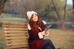 Mädchen, das mit Tablette auf Bank im Park sitzt Stockfoto